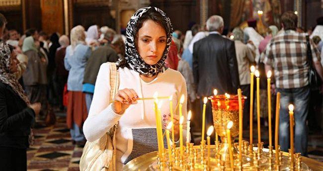Дівчина ставить свічку в церкві